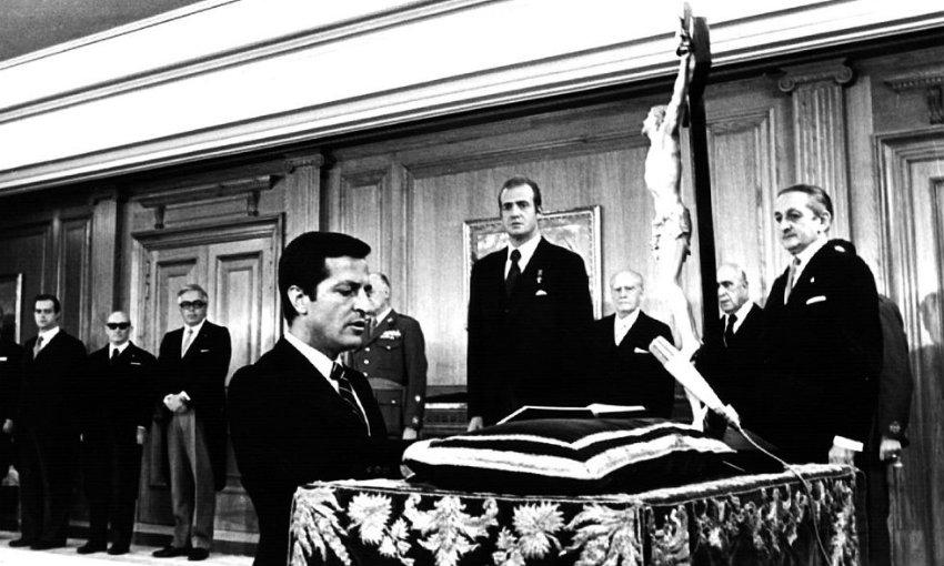 Adolfo Suárez jura arrodillado su cargo de presidente del Gobierno ante el Rey en el Palacio de la Zarzuela el 5 de julio de 1976. A la derecha se ve a Torcuato Fernández Miranda. (Foto: El País)